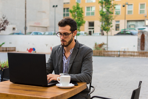 Young Businessman Is Working In A Bar Terrace With His Laptop And Smartphone Stock Photo - Download Image Now