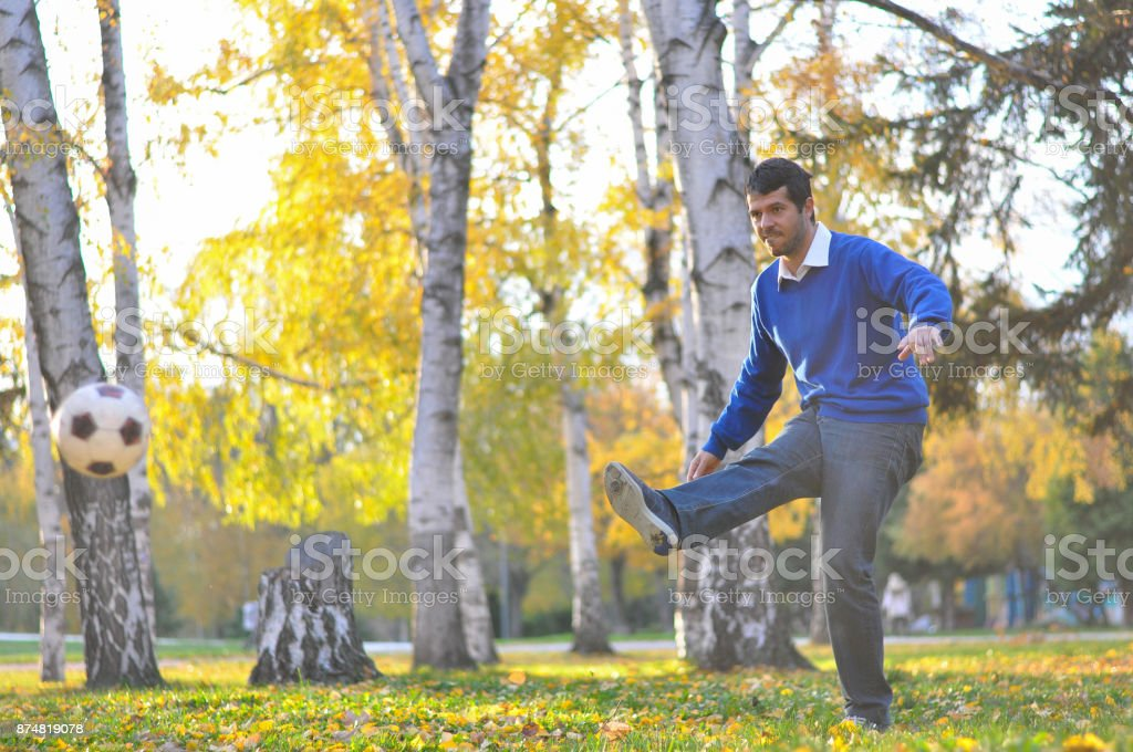 Young businessman kick the ball in park. stock photo