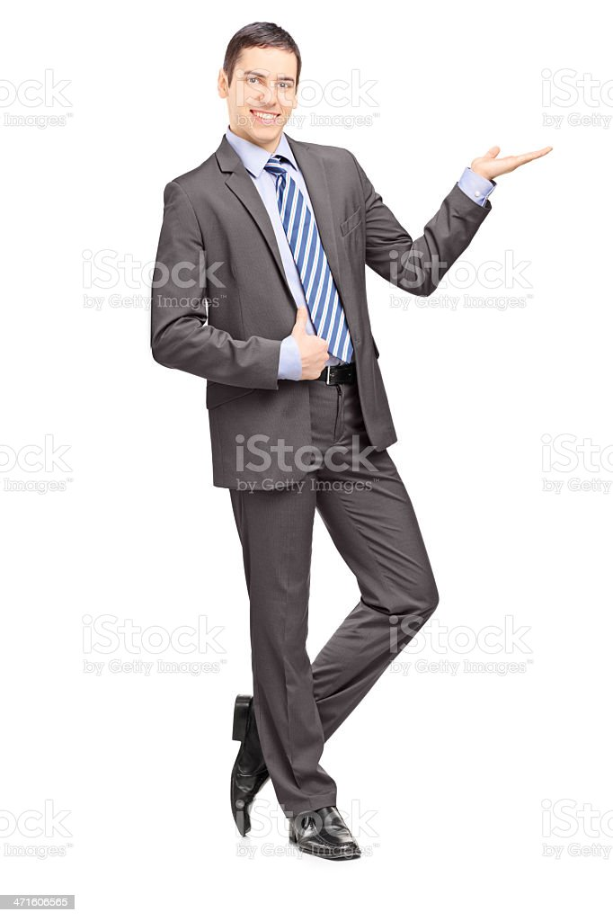 Young businessman leaning against wall and gesturing stock photo