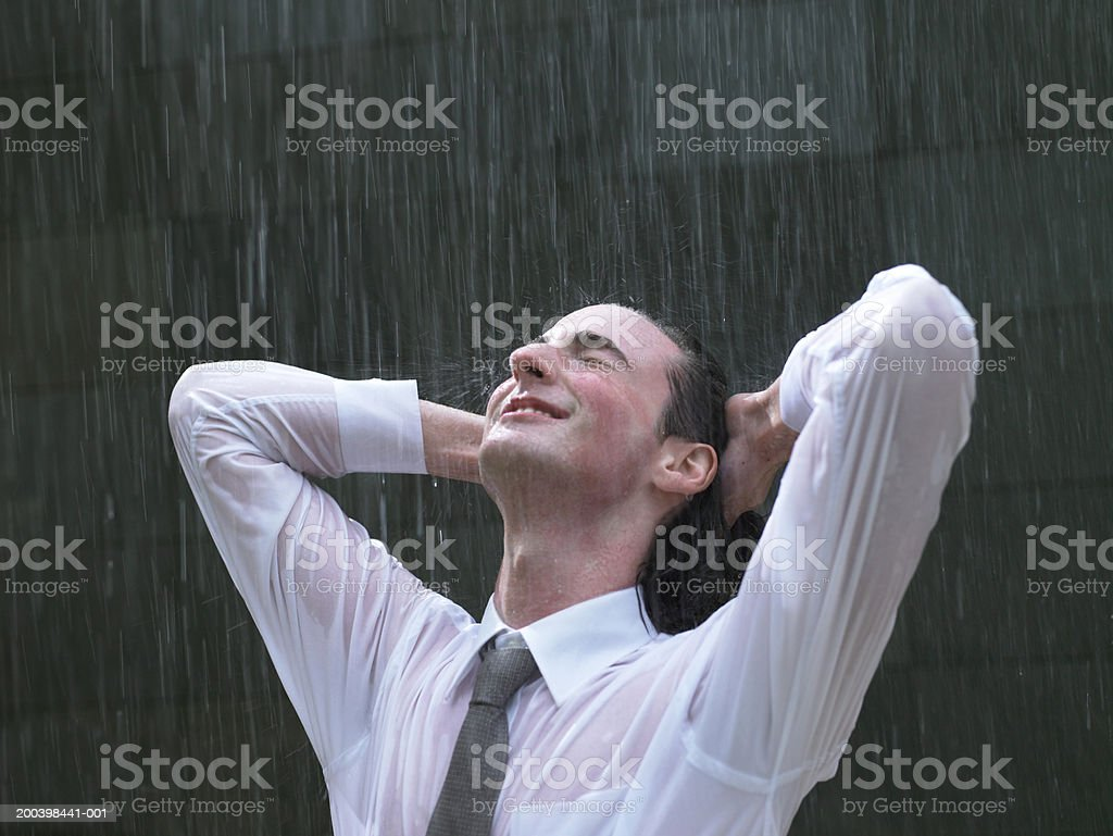 Young businessman leaning back in rain, hands behind head, eyes closed royalty-free stock photo