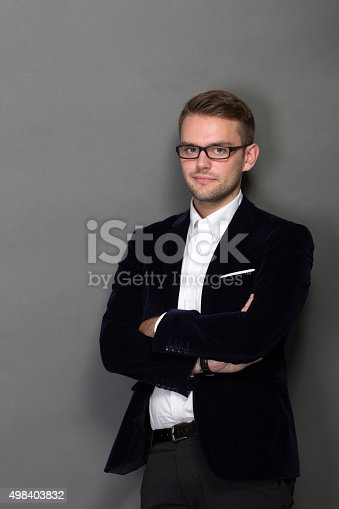 498403166 istock photo Young businessman leaning on the wall in work suit 498403832
