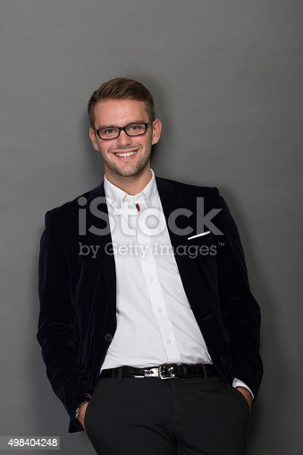 498403166 istock photo Young businessman leaning on the wall in work suit 498404248