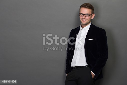 498403166 istock photo Young businessman leaning on the wall in work suit 498404456