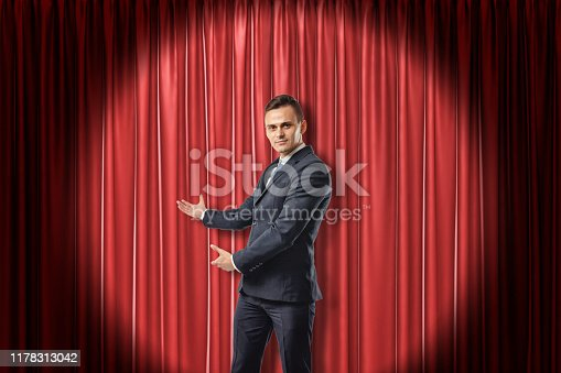 939155332 istock photo Young businessman lit up by limelight making a presenting gesture against red theater curtain. 1178313042