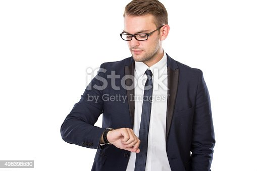498403166 istock photo Young businessman look at his watches, isolated 498398530