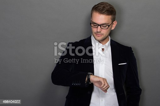 498403166 istock photo Young businessman look at his watches 498404022