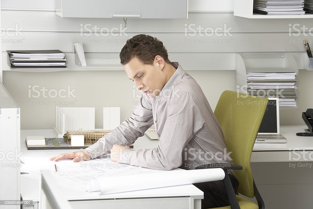 Young businessman looking at blue prints on desk royalty-free stock photo