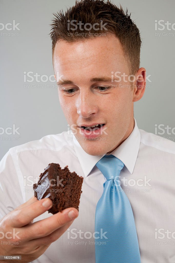 young businessman looking at chocolate cake stock photo