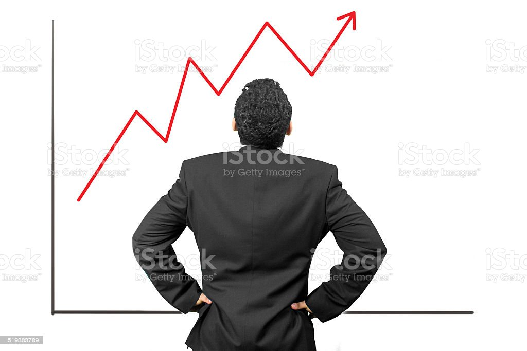 Young businessman looking at his growing share stock photo