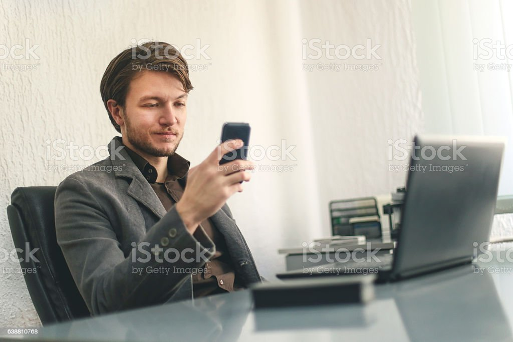 Young businessman looking at his phone stock photo
