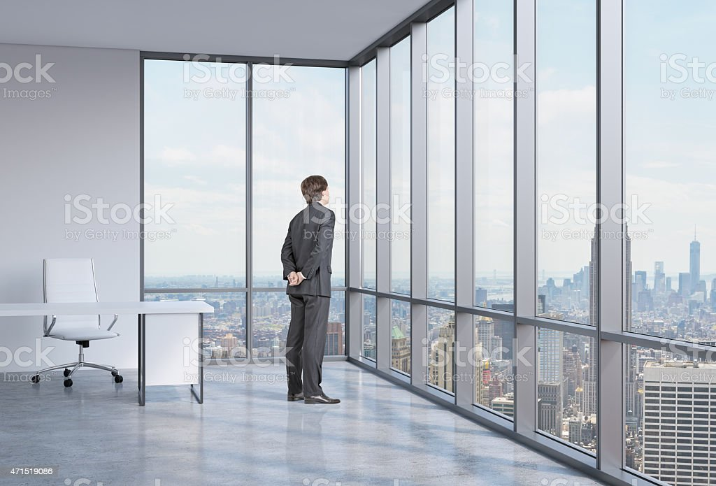Young businessman looking out an office window at the city stock photo