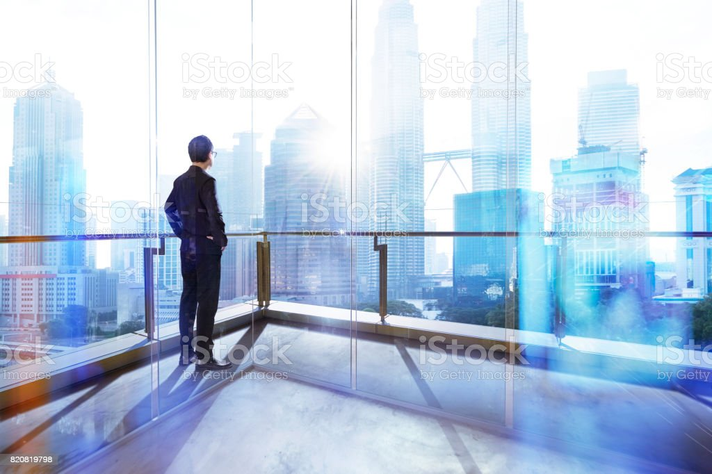 Young businessman looking out the city in the office . morning scene. . stock photo