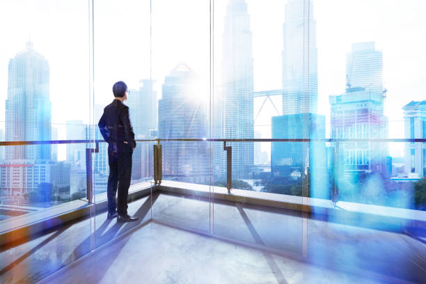 young businessman looking out the city in the office . morning scene. . - looking at view stock pictures, royalty-free photos & images