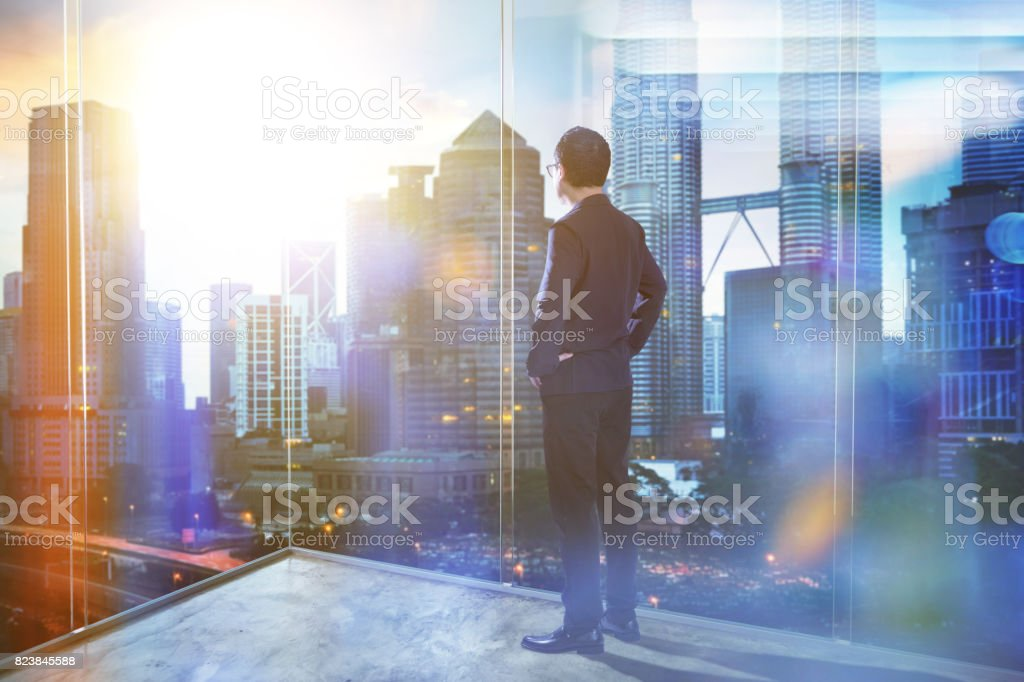 Young businessman looking out the city in the office . morning scene. . royalty-free stock photo