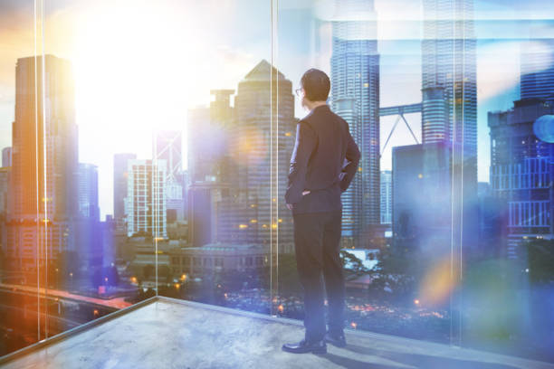 Young businessman looking out the city in the office . morning scene. . Young businessman looking out the city in the office . morning scene. . business Malaysia stock pictures, royalty-free photos & images