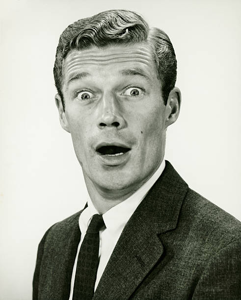 Young businessman looking surprised, posing in studio, (B&W), portrait stock photo