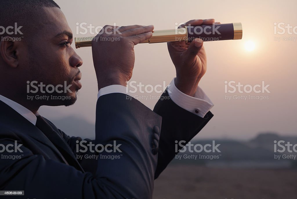 Young businessman looking through telescope in middle of the desert stock photo