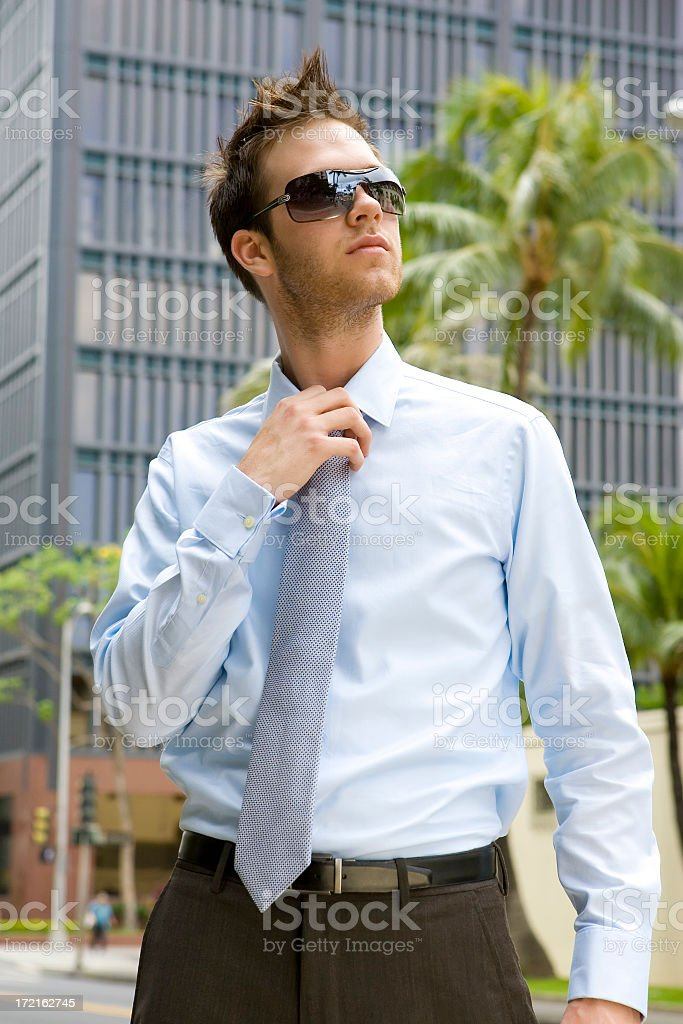 Young Businessman Loosening Tie stock photo