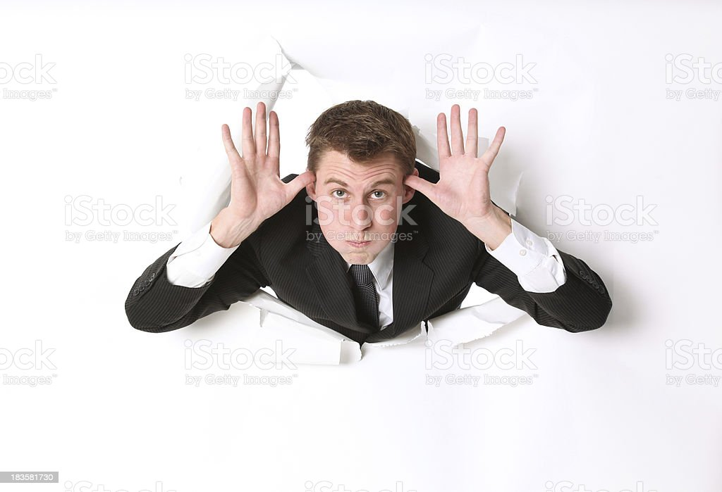 Young businessman making a silly face emerging through hole stock photo