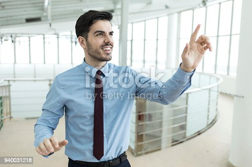 825082848istockphoto Young businessman making presentation at work 940031218