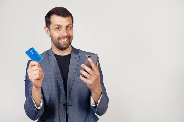 Young businessman man with a beard in a jacket, Handsome man using a credit card to pay online using a smartphone. Portrait of a man on a gray background stock photo