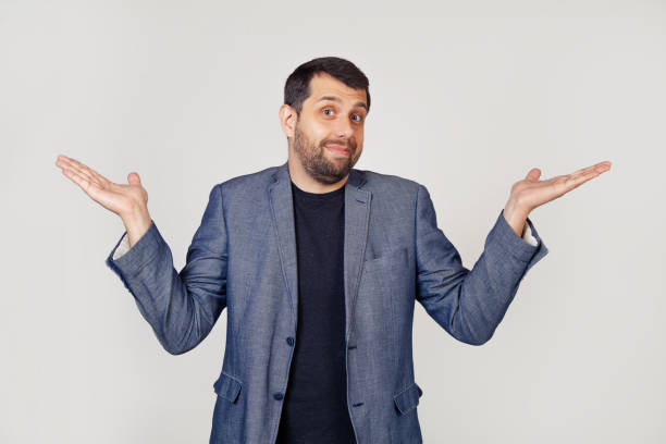 A young businessman man with a beard in a jacket, shrugs his shoulders, arms outstretched, complete disbelief, doubts to say the answer I have no idea. I dont know. stock photo