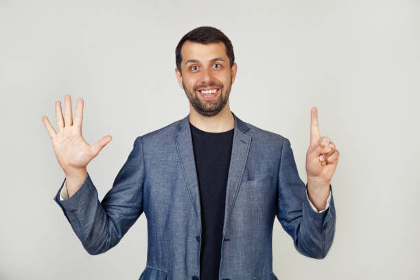 Young businessman man with beard smiling, showing number six with fingers on his hand, smiling confidently and happily, looking at the camera. stock photo
