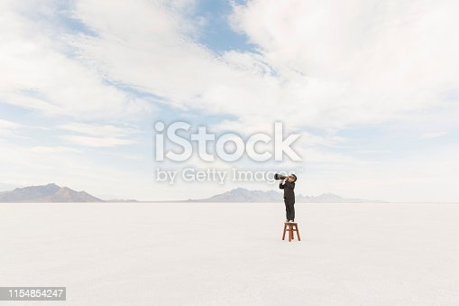 istock Young Businessman on a Stool with a Megaphone 1154854247