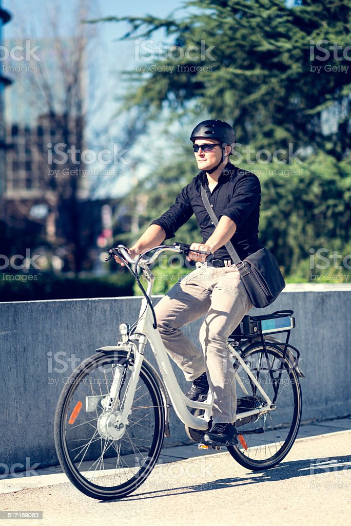 Young businessman on electric bicycle stock photo