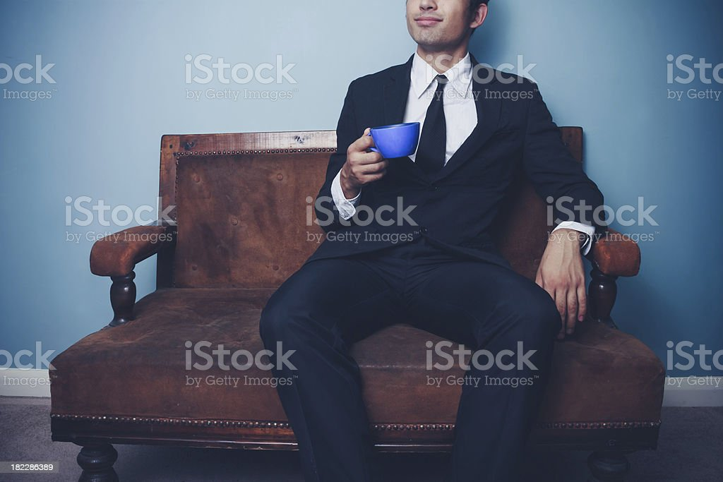 Young businessman on sofa drinking coffee royalty-free stock photo