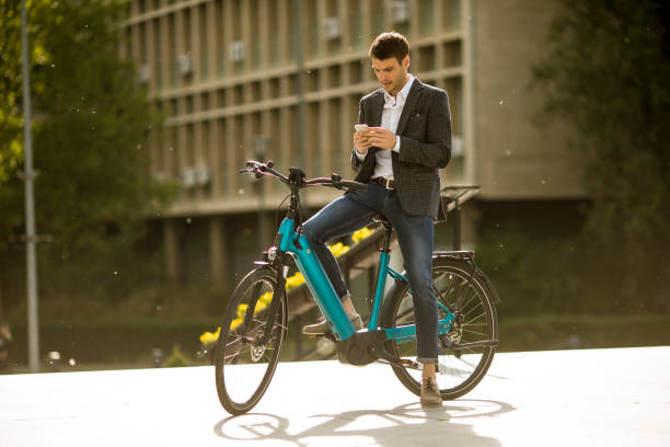 Young businessman on the ebike using mobile phone stock photo