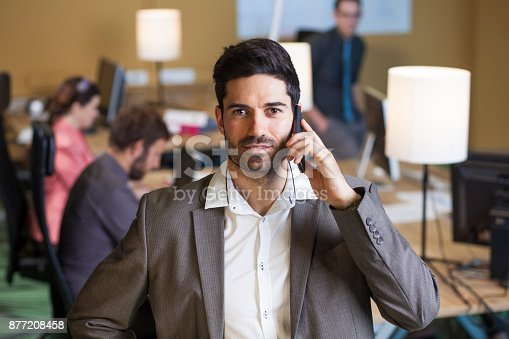 624700110istockphoto Young businessman on the phone in office with colleagues in background 877208458