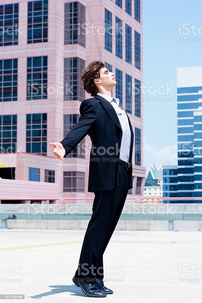 young businessman opening arms to the sun, buildings in background royalty-free stock photo