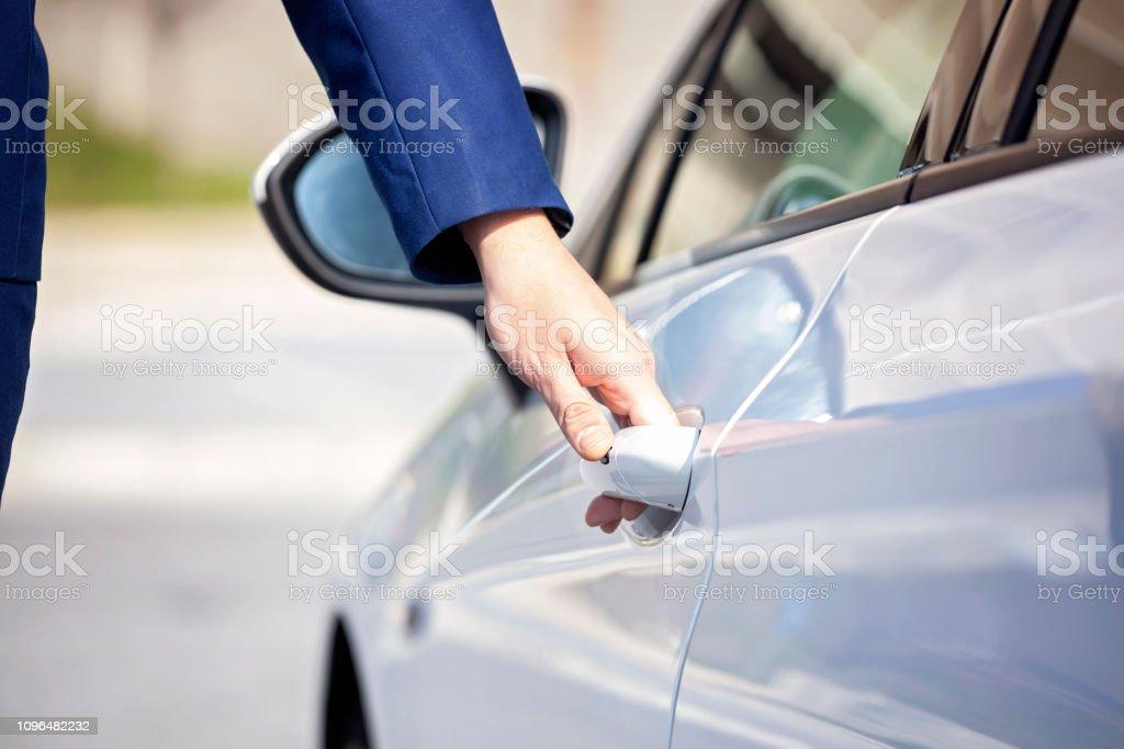 Beyaz arabanın kapısını açarak genç iş adamı. stok fotoğrafı