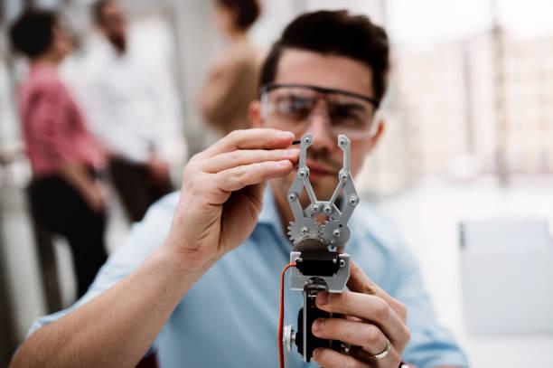 ein junger geschäftsmann oder wissenschaftler mit robotischer hand, die im amt steht, arbeitet. - erfinder der fotografie stock-fotos und bilder