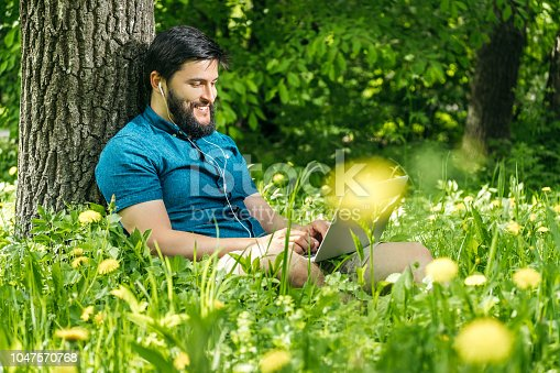 istock Young businessman or student in casual dress using laptop in the park. Outdoor office concept 1047570768