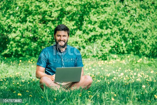 istock Young businessman or student in casual dress using laptop in the park. Outdoor office concept 1047573682