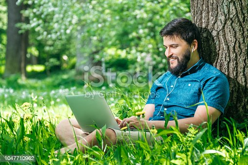 istock Young businessman or student in casual dress using laptop in the park. Outdoor office concept 1047710962