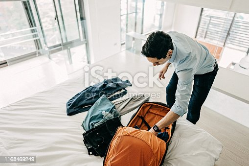 Young Businessman packing suitcase for business travel