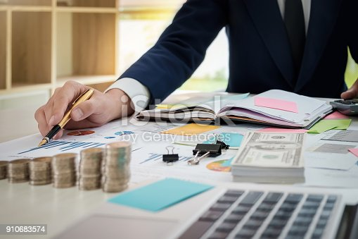 881542122istockphoto Young businessman pen pointing graph chart in this month with using post it note, laptop computer and notebook for  Plans to improve quality next month in his office. 910683574