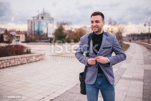Portrait of a happy young man in casual clothes looking at a cellphone outside. Smiling man with a beard who feels confident. Successful business man on city street.