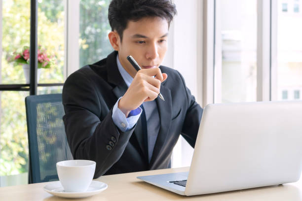 young businessman Handsome adult, confident smart, young businessman working in a new office. he used a technology smartphone, tablet, computer and relax at break time in a small financial company handsome asian boss in the office stock pictures, royalty-free photos & images