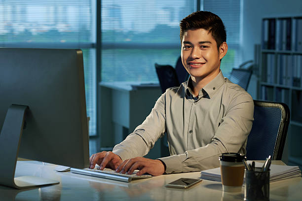 Young businessman Portrait of cheerful Filipino businessman  at his workplace filipino ethnicity stock pictures, royalty-free photos & images