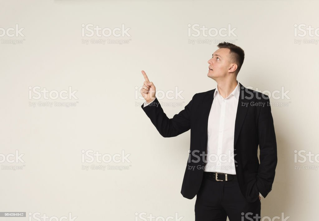 Young businessman pointing upwards with hand - Royalty-free Above Stock Photo