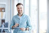 Waist up portrait of handsome young man holding digital tablet and smiling happily at camera standing by window, copy space