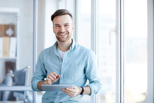 joven empresario posando por window - un solo hombre joven fotografías e imágenes de stock