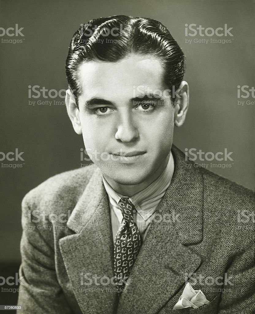 Young businessman posing in studio, (B&W), portrait stock photo