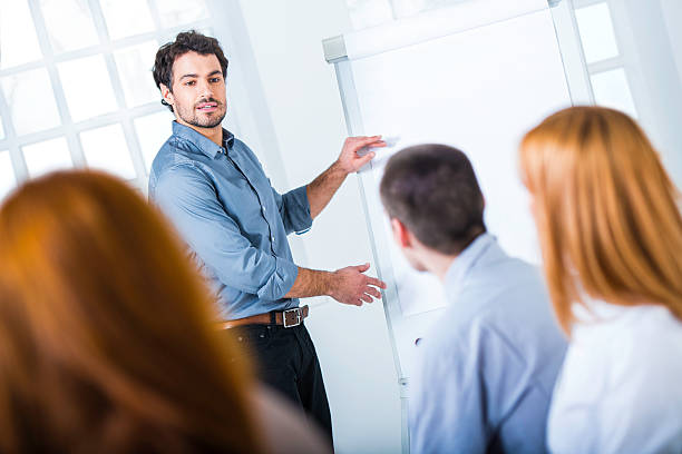 Young Businessman Presenting His Ideas on Flip Chart to Colleagues Young businessman giving a lecture to a group of business people at conference room. flipchart stock pictures, royalty-free photos & images