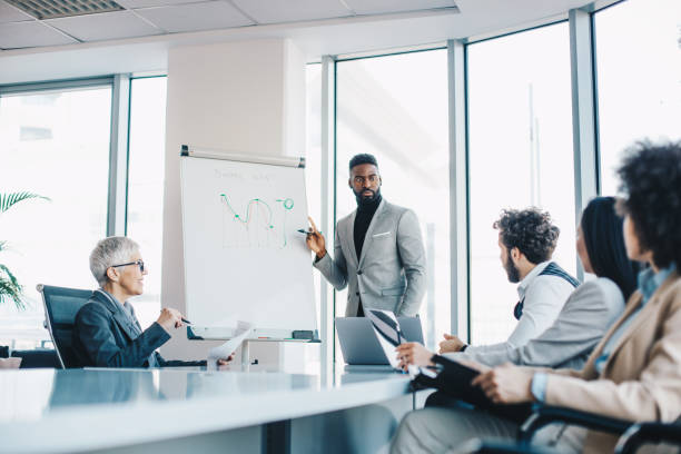 A young businessman presenting to a managerial team his ideas over a graph on a whiteboard at the conference room. He has a plan on how to improve the results. stock photo