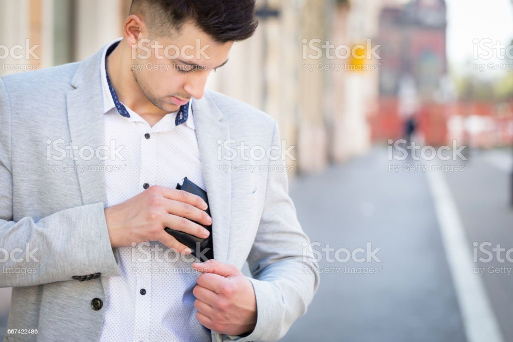 young businessman pull out his wallet stock photo
